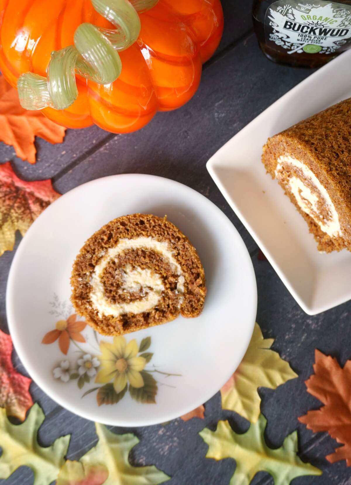 Overhead shoot of a small plate with a slice of pumpkin roll, colourful leaves, another plate with more roll and a pumpkin