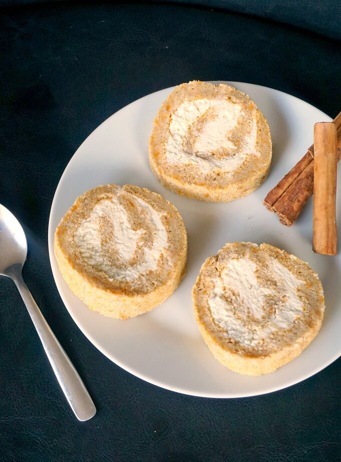 3 pumpkin rolls and 2 cinnamon sticks on a white plate, and a teaspoon on the side