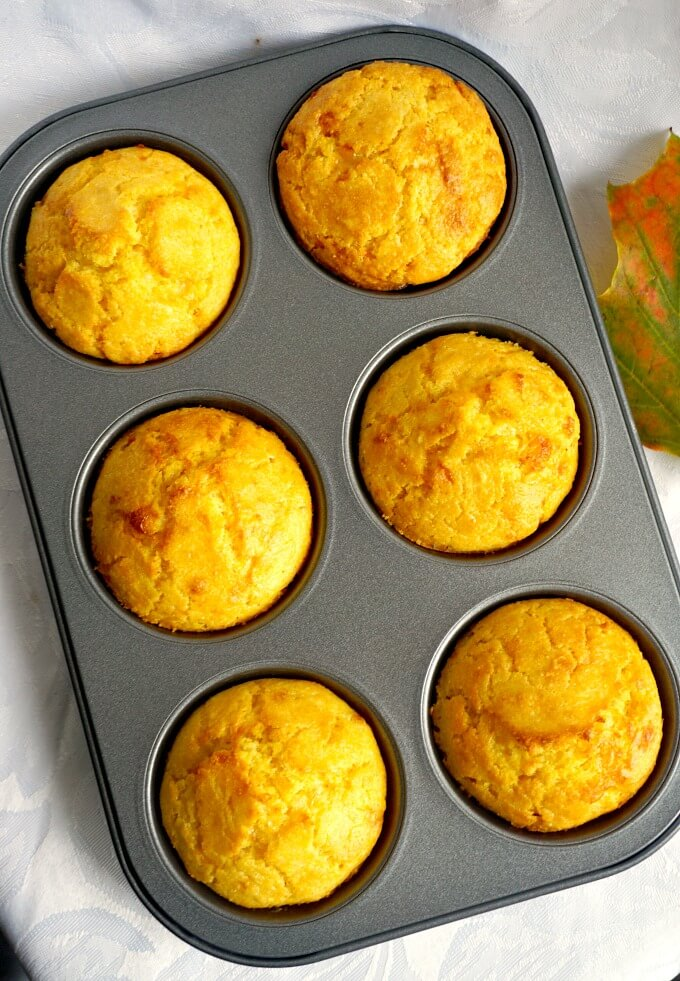 Overhead shoot of a 6-hole muffin tin with 6 cornbread muffins