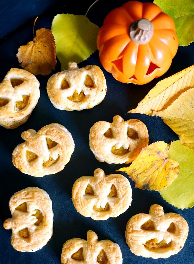 Overhead shoot of 7 Jack-O'-Lantern Pumpkin Hand Pies, a pumpkin and leaves on a black table top