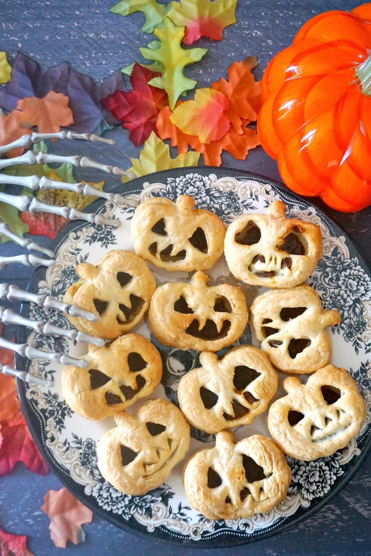 Overhead shoot of a plate with pumpkin hand pies with Halloween decorations around