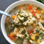A white bowl with chicken and barley soup