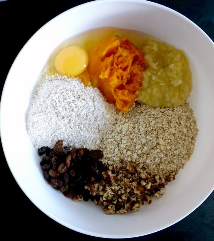 A white bowl with ingredients needed to make pumpkin oatmeal bars