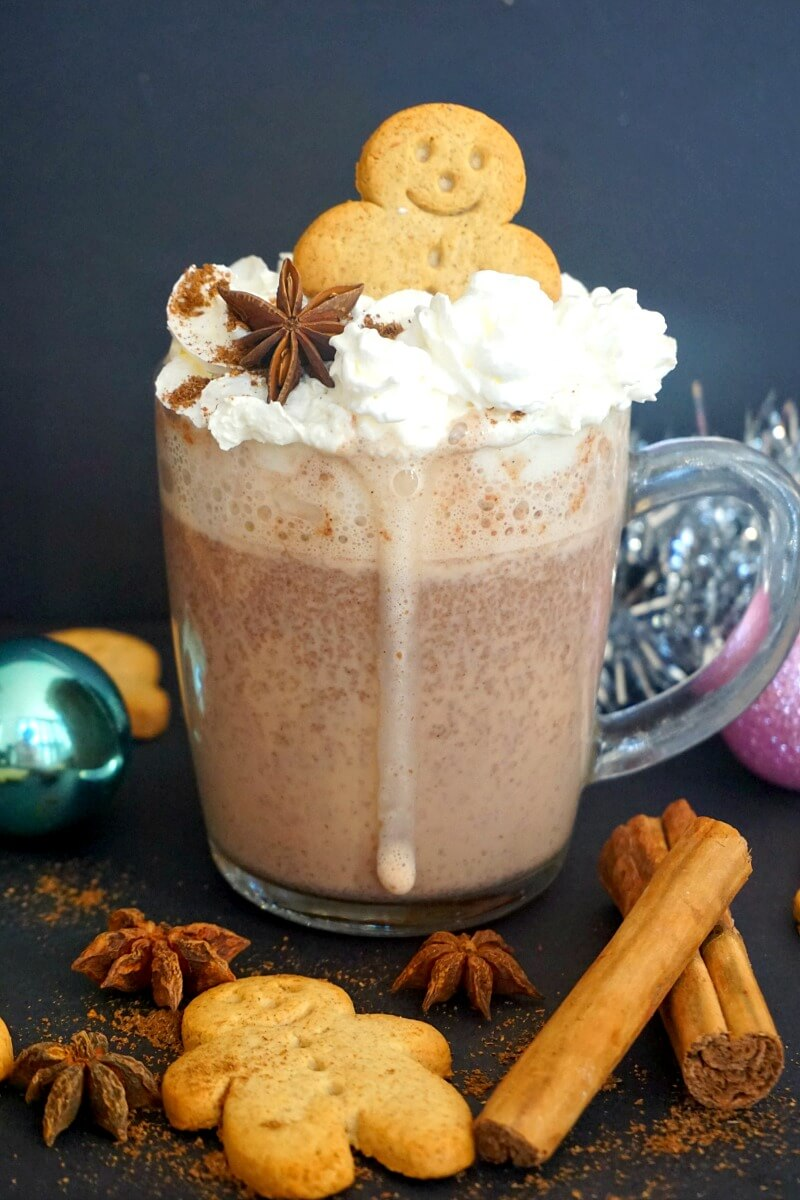 A cup of Gingerbread Hot Chocolate topped with cream and a gingerbread man cookie