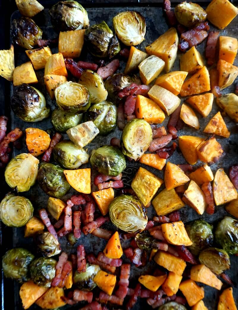A tray with roasted sprouts, sweet potatoes and bacon