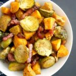 Overhead shot of a white dish of Maple Roasted Brussel Sprouts with Bacon and Sweet Potatoes