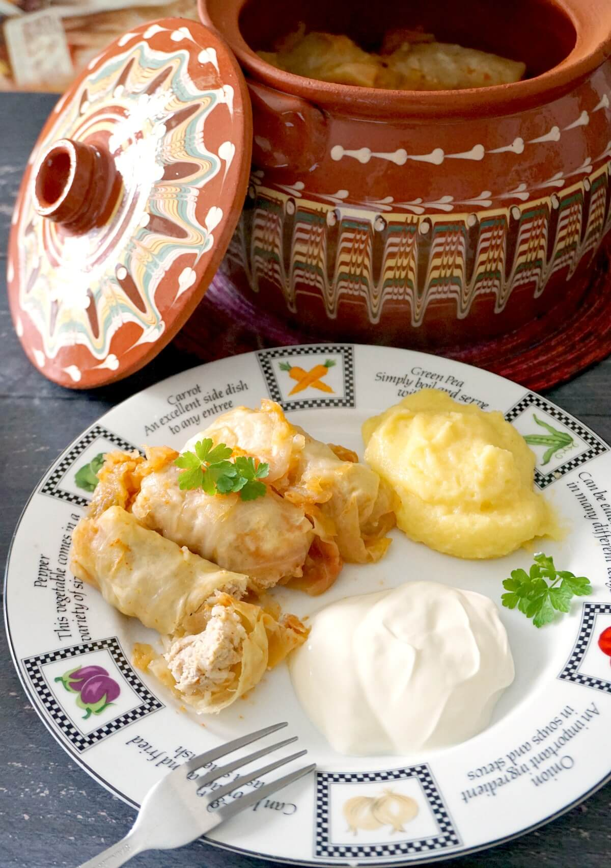 A plate with 3 cabbage rolls, polenta and sour cream and a pot of sarmale in the background