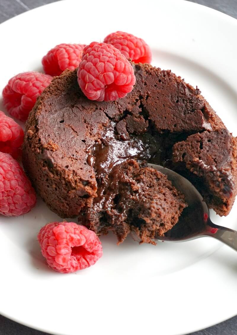 An individual chocolate lava cake with raspberries on a white plate