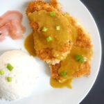 Overhead shot of a white plate with rice, pcikled ginger, and 2 breaded chicken fillets with japanese katsu curry