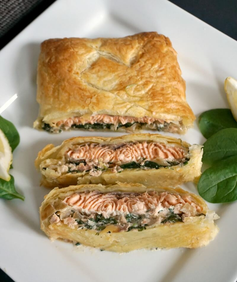 3 slices of Salmon Wellington on a white plate