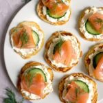 Overhead shot of a white round plate with 7 smoked salmon blini canapes