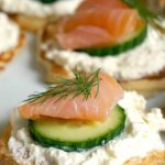 Smoked Salmon Blini Canapés, the perfect party food for your Christmas or New Year's Eve dinner, or any other party around the year. Delicious homemade blinis topped with silky cream, cucumber, smoked salmon and a touch of lemon; can't think of a better appetizer! These blinis are very easy to make, and can be topped with anything else that takes your fancy. #blinis, #canapes, #christmasfood, #newyearseveparty
