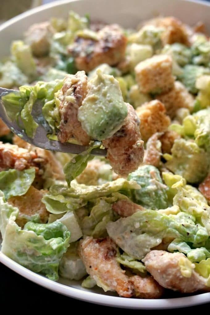Close-up shoot of a white bowl of grilled chicken caesar salad