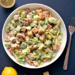 Overhead shoot of a white bowl of chicken caesar salad, a fork on the side, a few cruttons, one lemon and a half a lemon