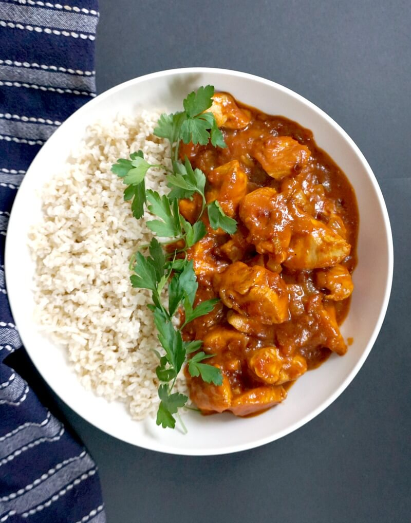Overhead shoot of a white plate with chicken curry, rice and parsley leaves