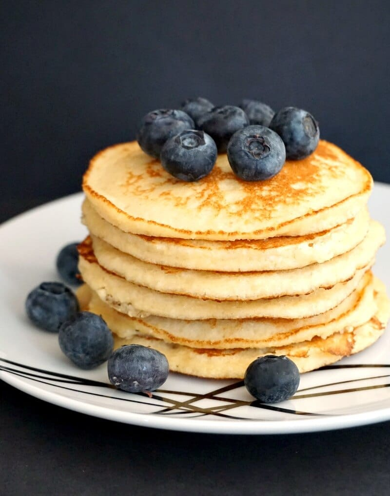 A pile of 6 almond pancakes topped with blueberries