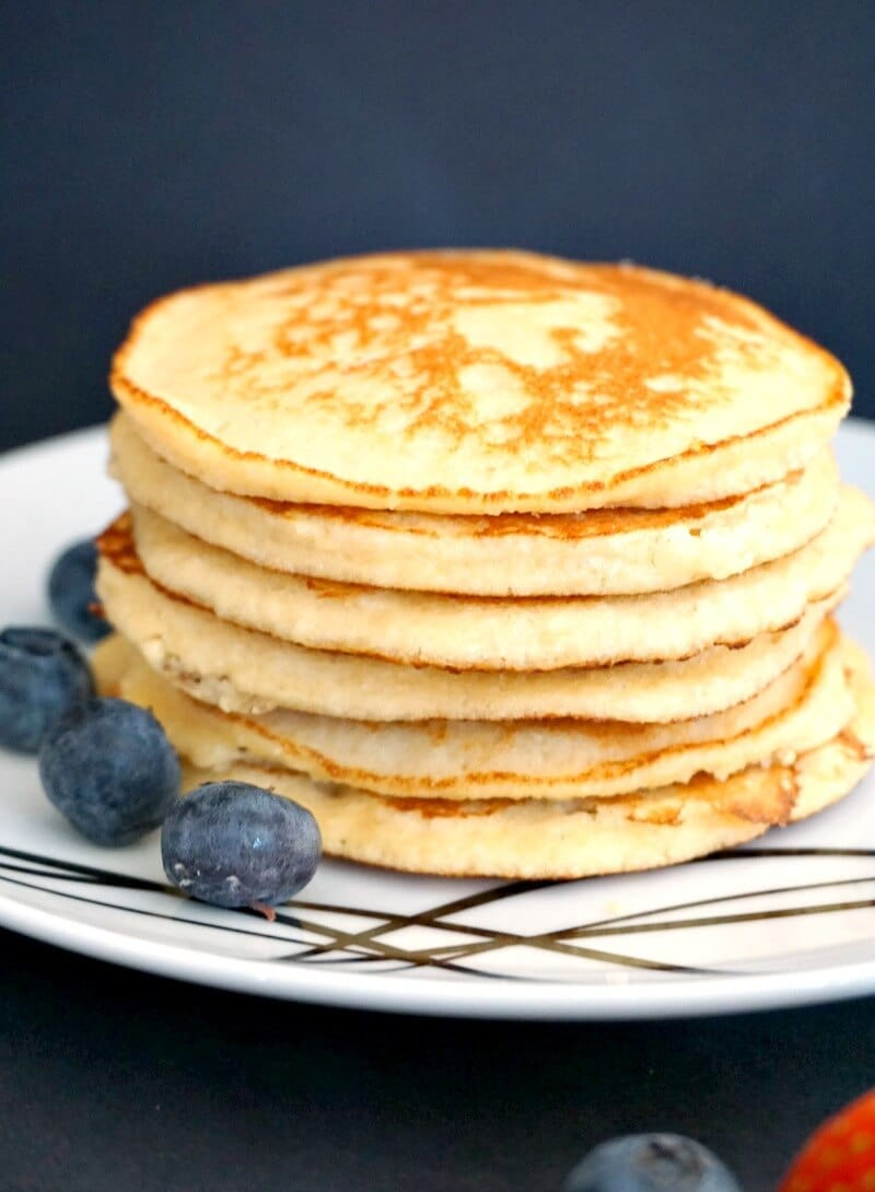 A stack of 6 almond pancakes with blueberries around the plate