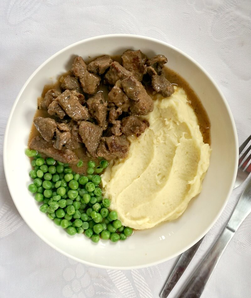 Overhead shoot of a white plate with beef tips and gravy, creamy mash and peas