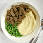 Overhead shoot of a white bowl with mash, peas and beef tips and gravy cooked in the slow cooker
