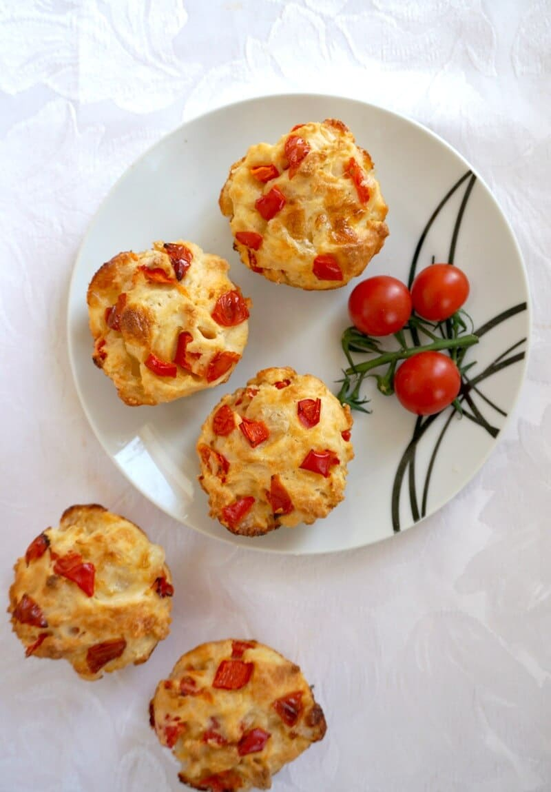 Overhead shoot of a white plate with 3 savoury muffins and 3 cherry tomatoes, and 2 other muffins on the side
