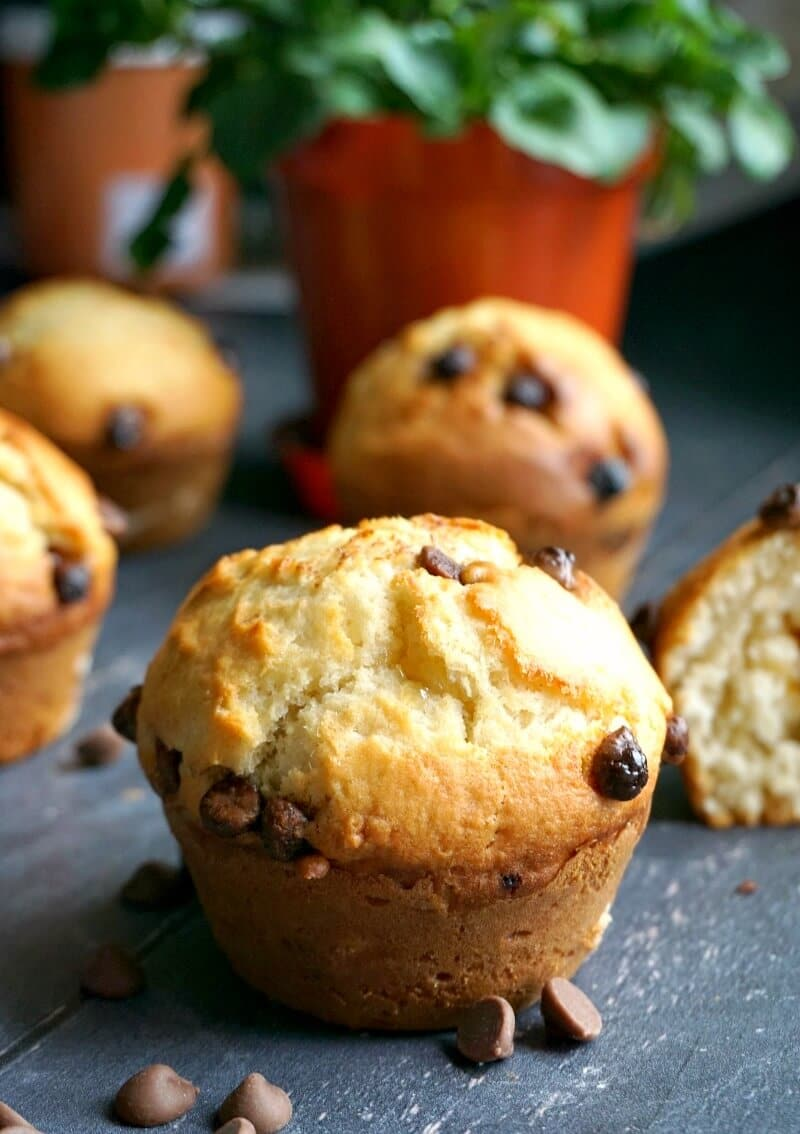 A chocolate chip muffin with more muffins around