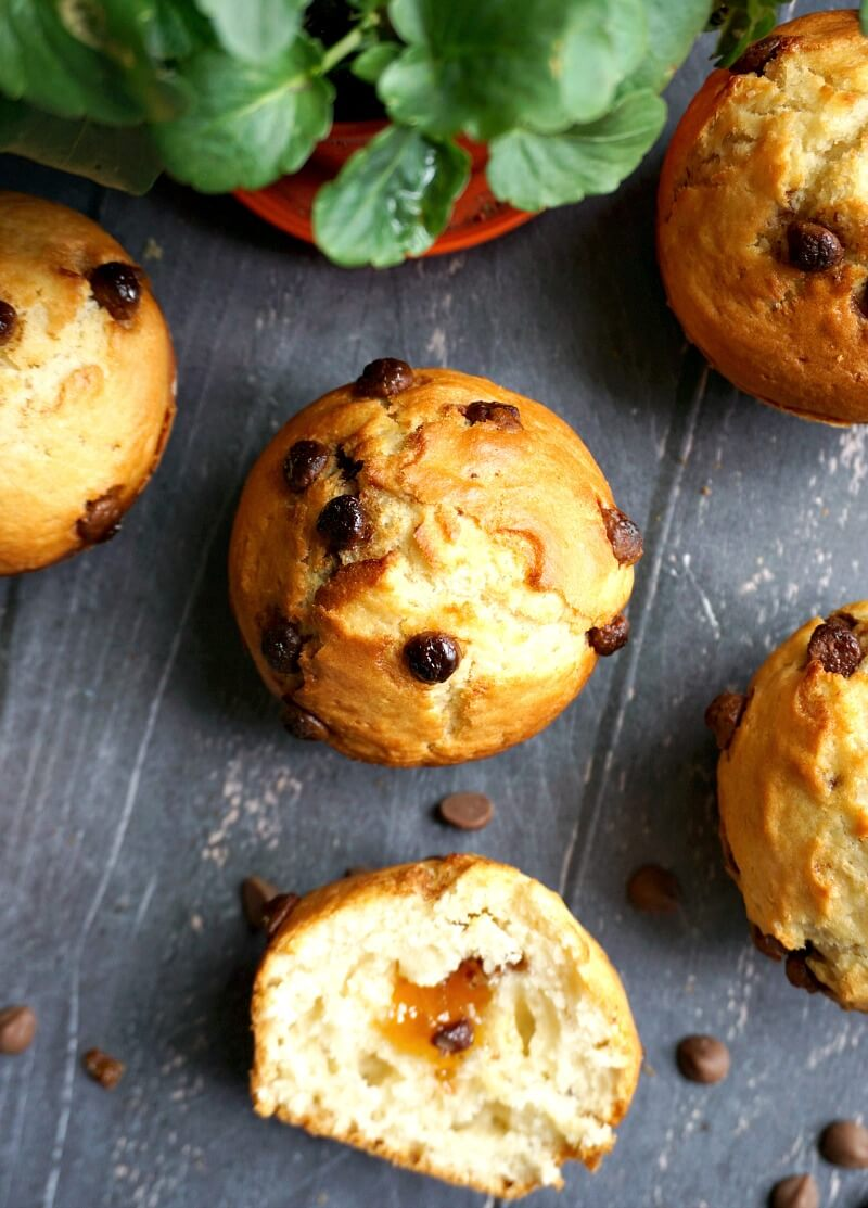 Overhead shoot of 2 muffins, a half muffin and a plant on a black tabletop