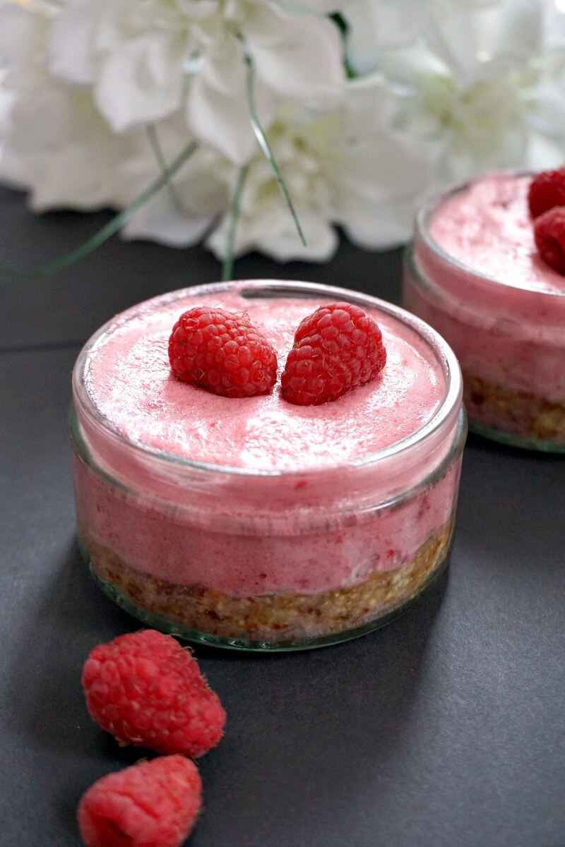 A pot of raspberry mousse cheesecake topped with 2 fresh raspberries