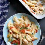 Overhead shoot of a light blue plate with chicken pasta bake, and a dish of more pasta