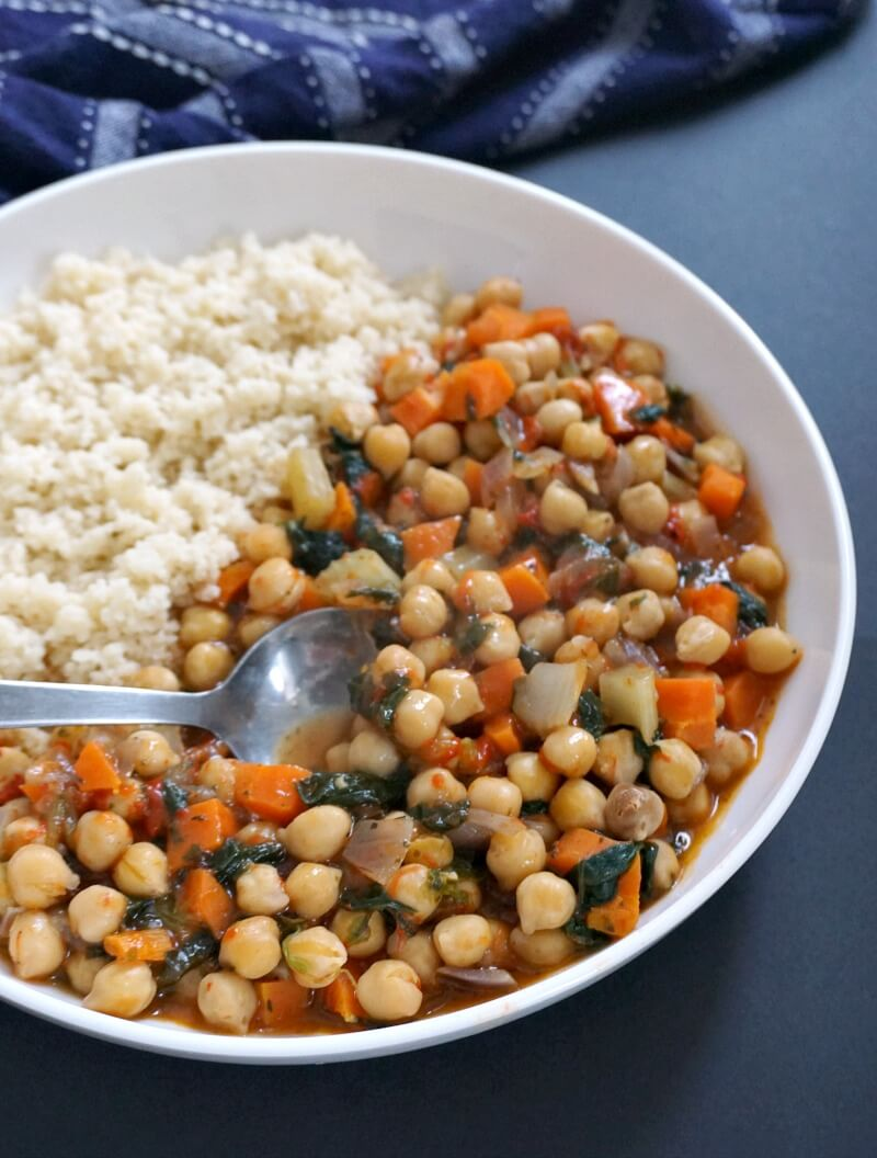 Close-up shoot of a white plate with vegan chickpea stew and bulgur wheat