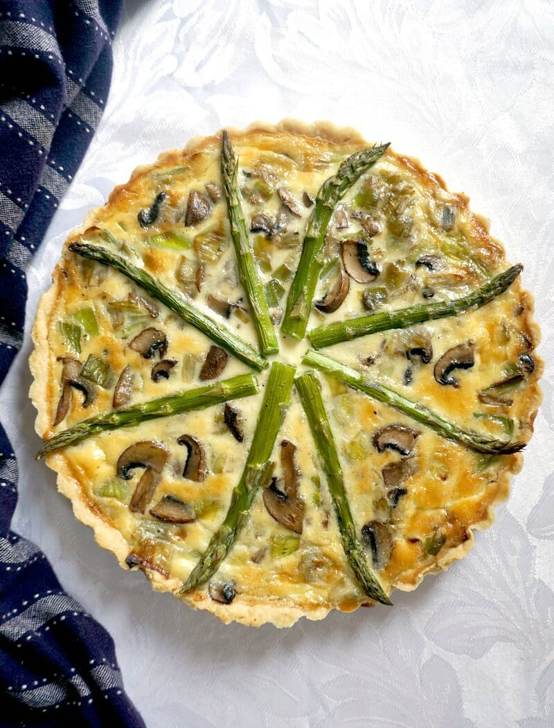 Overhead shoot of a quiche with asparagus, mushrooms and leeks