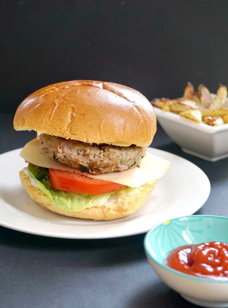 A white plate with a turkey burger, a small blue bowl with ketchup and a white bowl with fries in the background