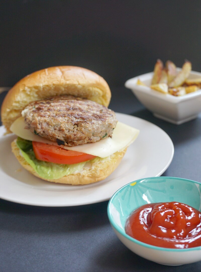 A white plate with a turkey burger in a bun with a slice of cheese, tomato and lettuce