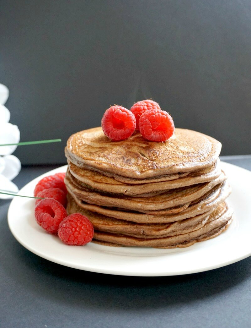 A white plate with a stack of chocolate pancakes toppd with raspberries