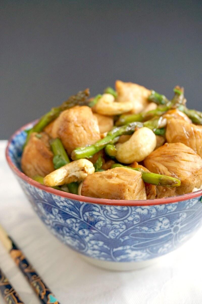 A blue bowl of chicken and asparagus stir fry