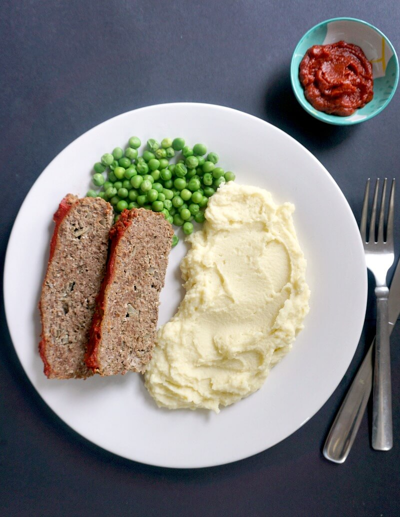 A white plate with 2 meatload slices, peas and mashed potatoes, a fork and a knife on the side and a small bowl of sauce at the top