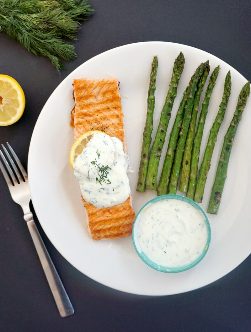 Overhead shoot of a white plate with a salmon fillet topped with yogurt dill sauce, grilled asparagus on the side and a small bowl with more sauce