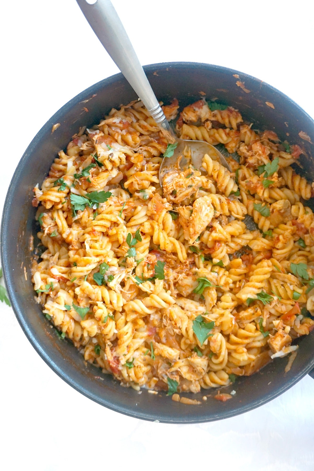 Overhead shoot of  pan with cheesy chicken pasta and parsley