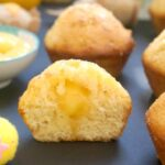 Half of a lemon drizzle muffin to show the lemon curd in the middle