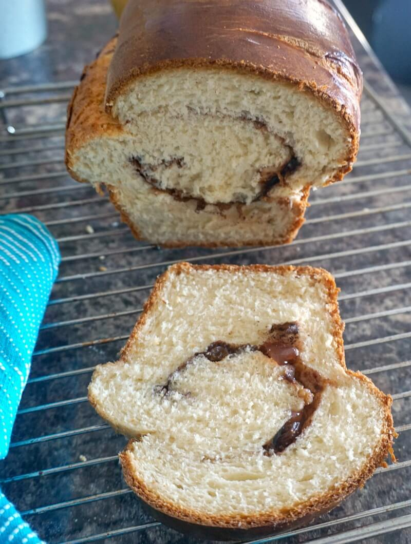 A slice of sweet bread and the remaining cozonac on a cooling rack
