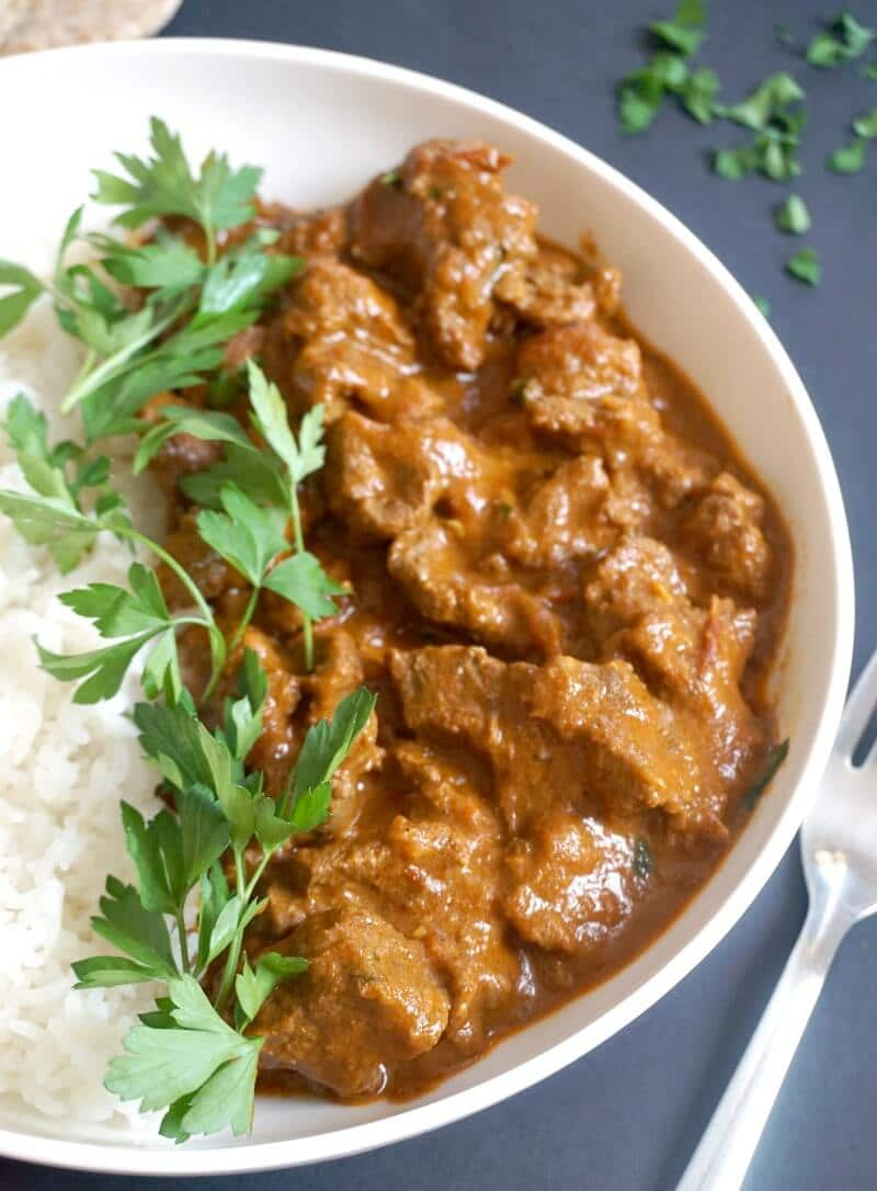A white plate with basmati rice and beef curry garished with parsley leaves