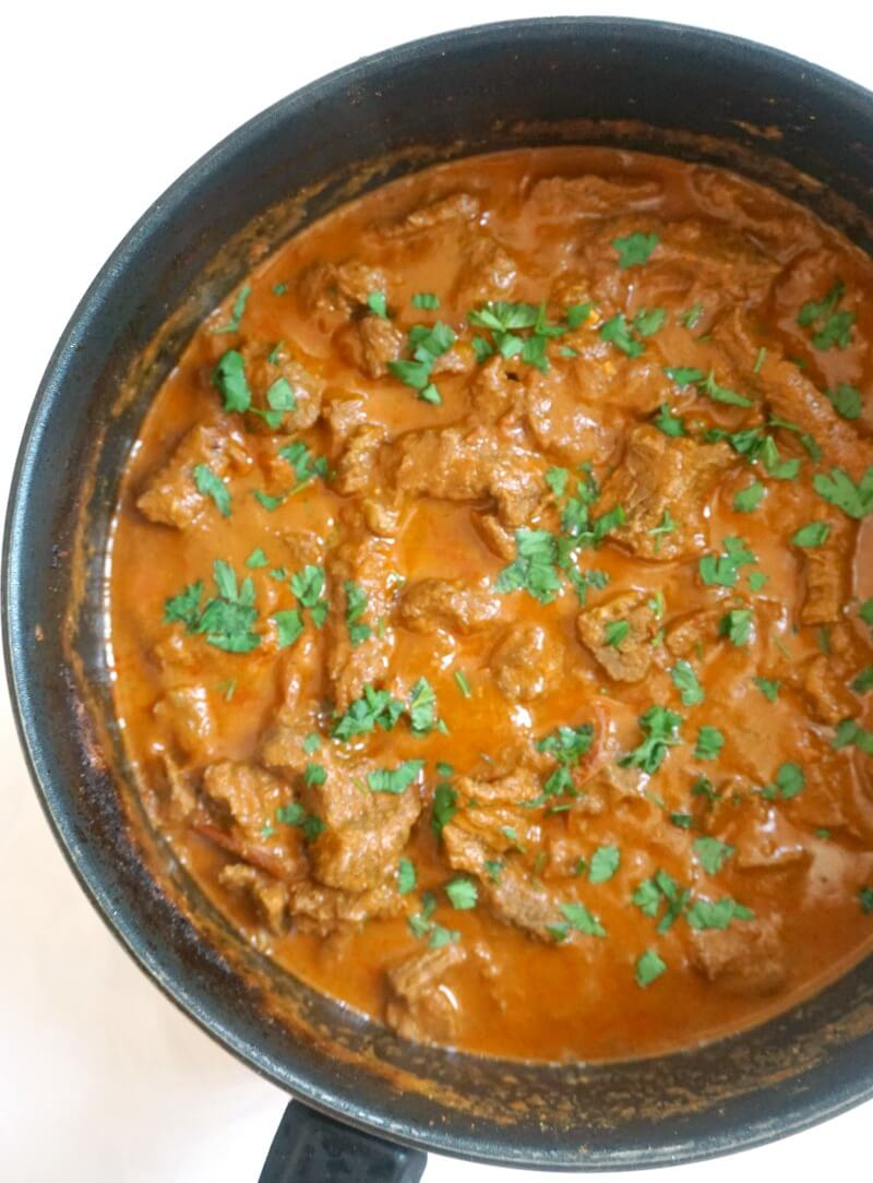 Overhead shoot of a pan with beef curry garmished with chopped parsley