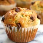 A zucchini muffin with chocolate chips with other muffins in the background