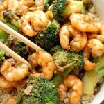 Honey Garlic Shrimp with Broccoli over a bed of rice, a super healthy stir fry that is packed with fantastic flavours. Quick and easy to make, and perfect for a midweek dinner for two, my shrimp stir fry is the best homemade Chinese-style dish you can get. Marinating the shrimp/prawns beforehand enhances the flavours, so not to skip this step. Otherwise, you can get the it ready real quickly in the skillet or even oven. #shrimp, #prawns,#stirfry, #chinesefood, #honeygarlicshrimp, #healthydinner