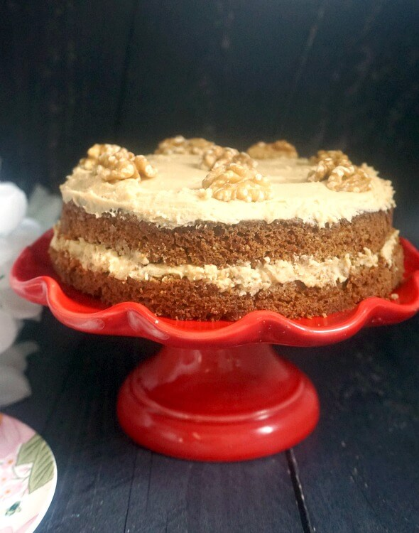 A red cake stand with a coffee and walnut cake on it