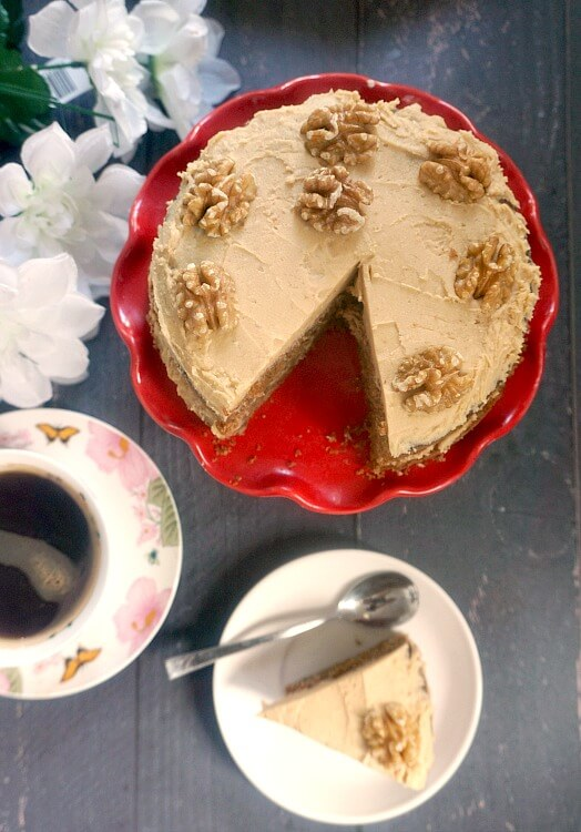 Overhead shoot of a red cake stand with a coffee and wlanut cake, a cup of coffee, white flowers and a white plate with a piece of cake on it