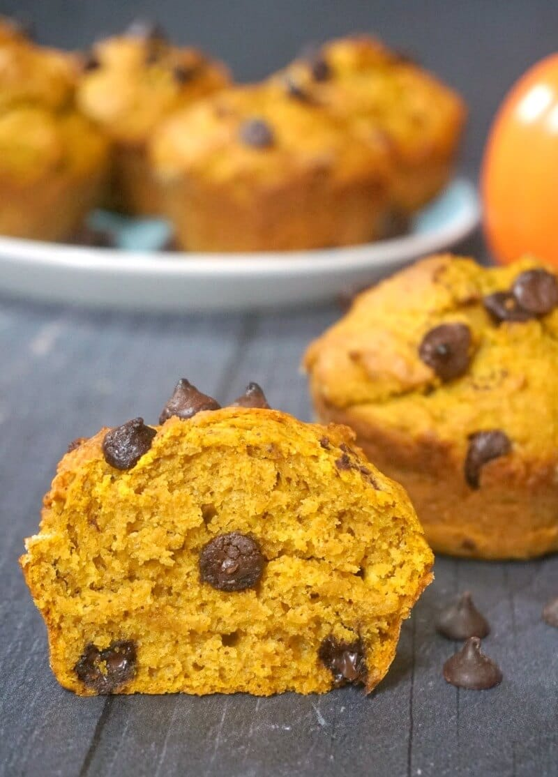 Half of a pumpkin and chocolate chip muffin with a whole muffin and a plate of other muffins in the background