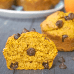 Hlaf of a pumpkin and chocoalte chip muffin with a whole muffin in the background