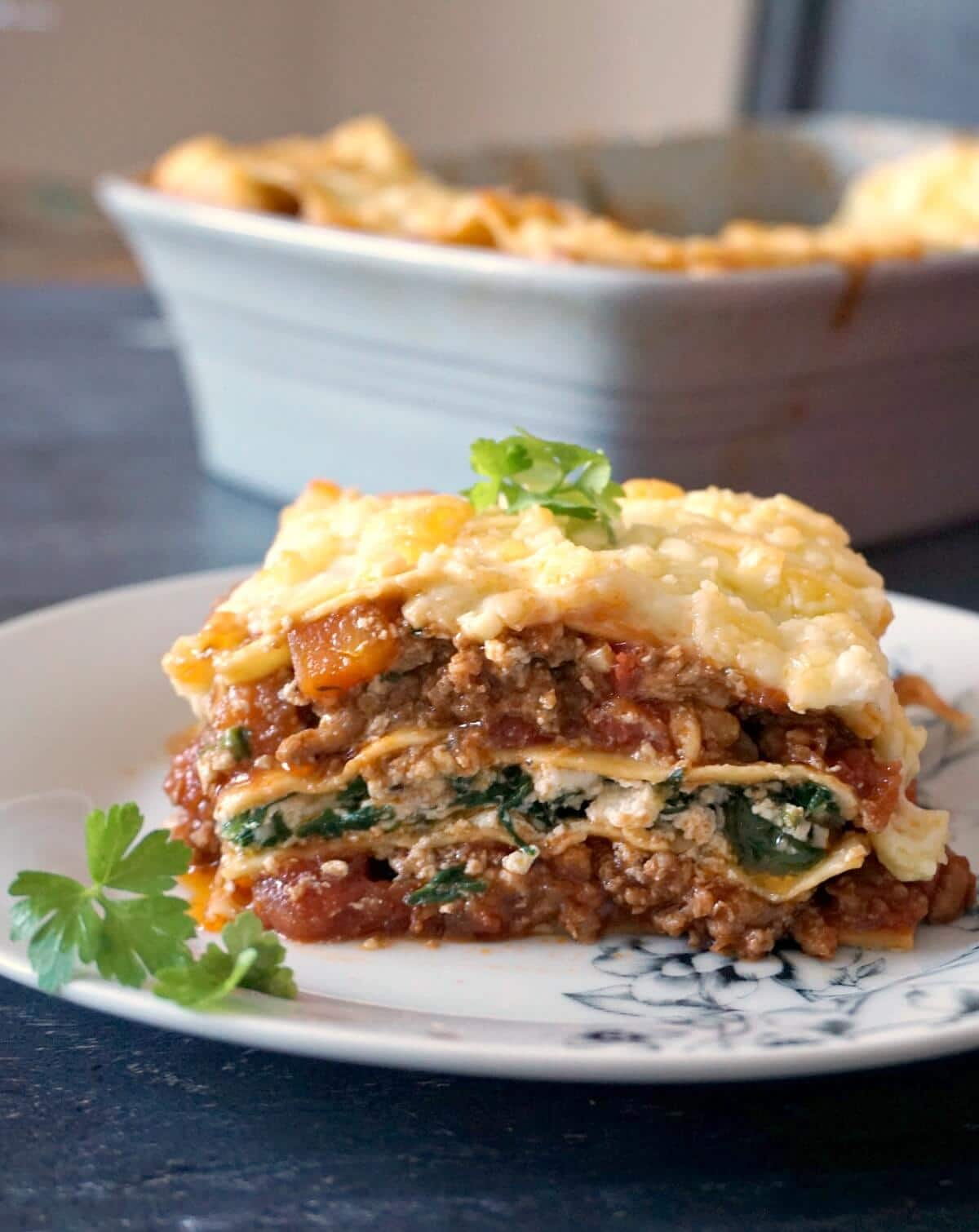 A slice of lasagna on a white plate garnished with fresh parsley leaves