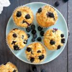 Overhead shoot of a blue plate with 5 blueberry muffins and fresh blueberries scattered around