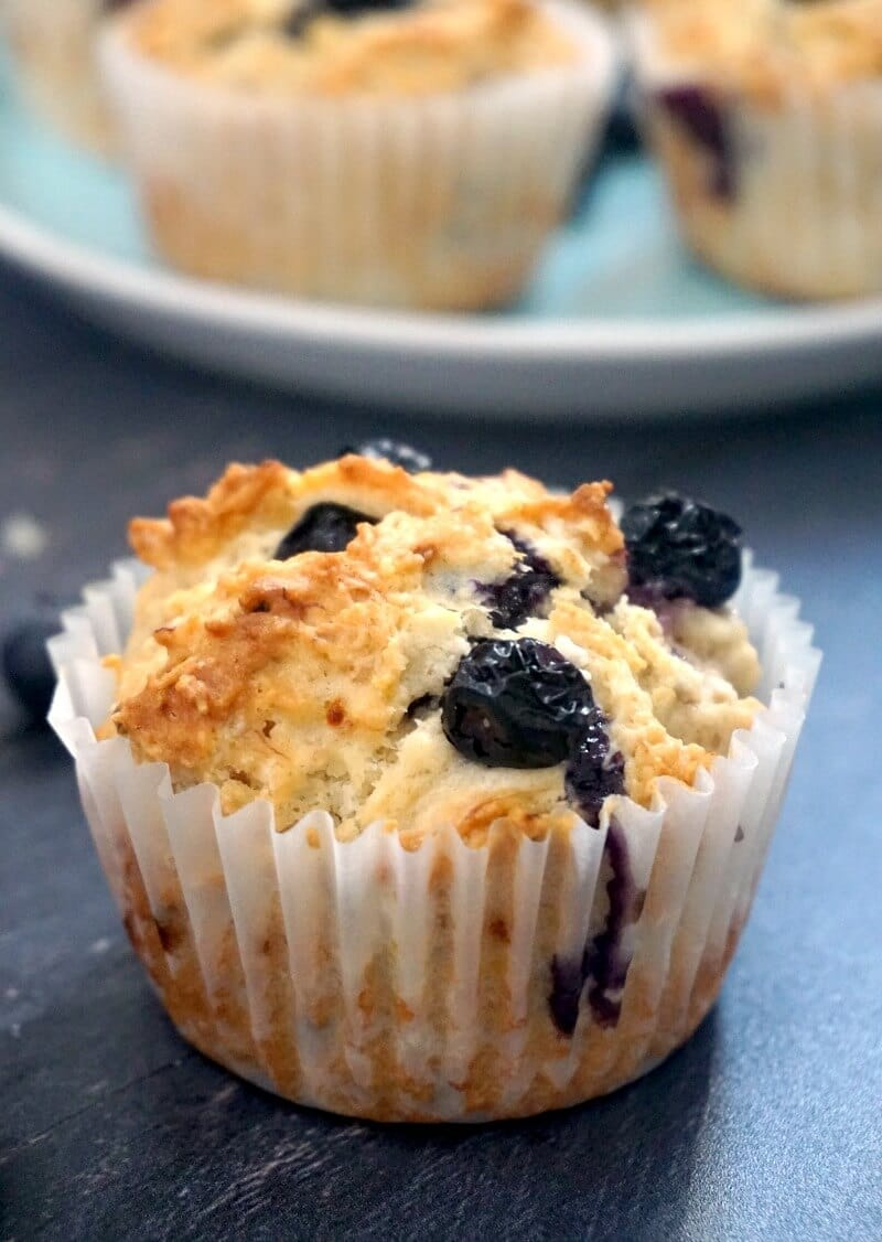 A blueberry muffin with a plate of other muffins in the background